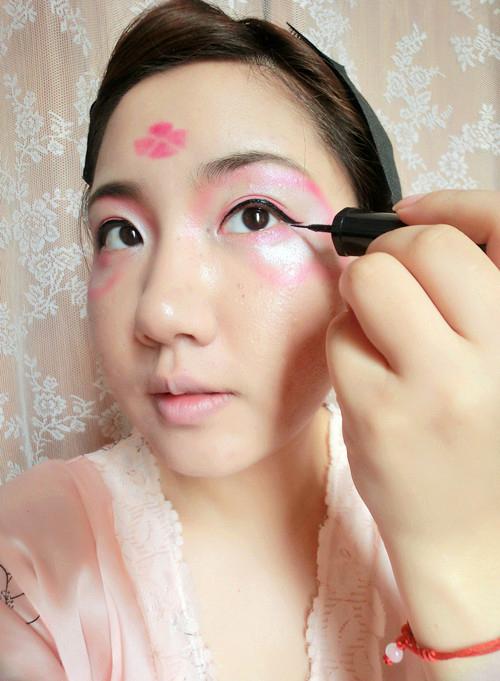 待到桃花图案初步完成后用眼线笔画出一条眼线 唇部的点缀由于没有唇
