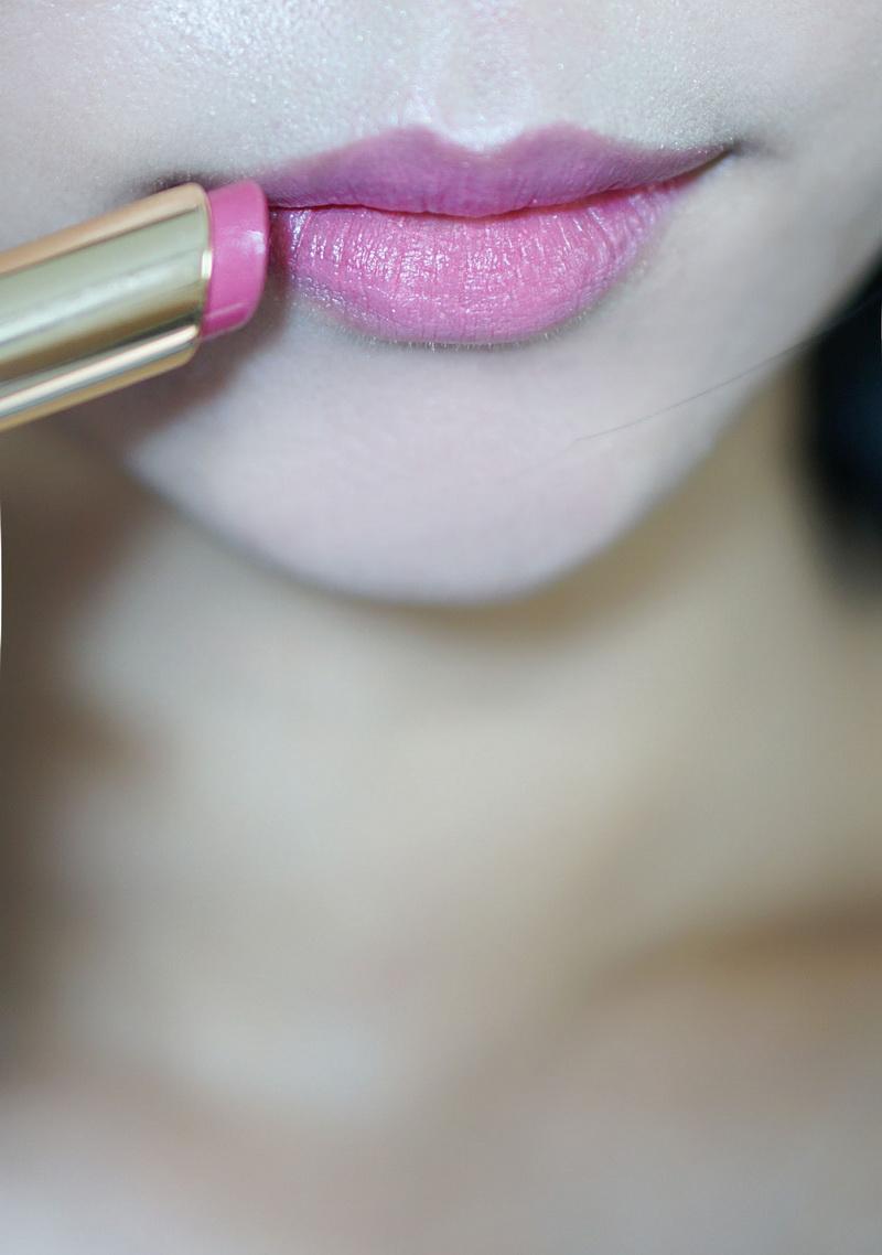 口红先用雅诗兰黛的粉色系口红打底,最后用唇彩或者润唇蜜在下唇中央